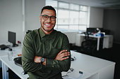 Portrait of a happy confident young african american businessman standing with his arms crossed looking at camera