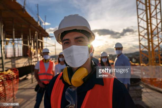portrait of a happy construction worker at a building site - building contractor stock pictures, royalty-free photos & images