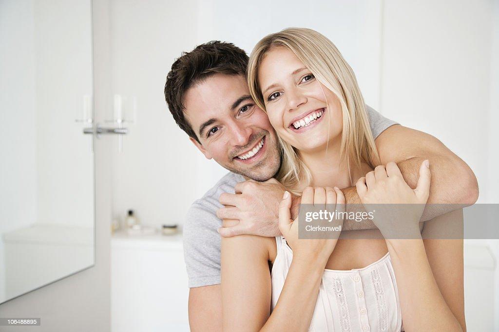 Portrait d'un couple heureux embrassant dans la salle de bains : Photo