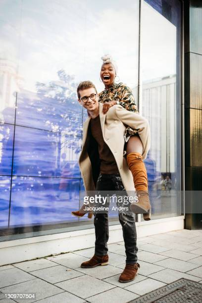 portrait of a happy couple in the city - the man gives her a piggyback ride - dancing stock pictures, royalty-free photos & images