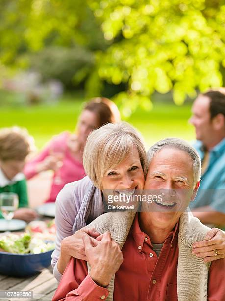 Portrait of a happy couple on picnic with family in background