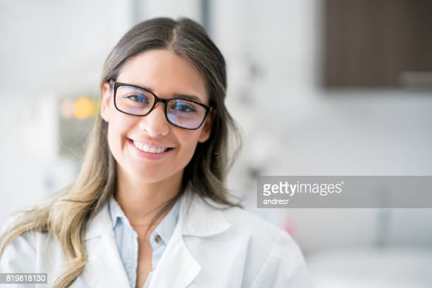 portrait of a happy doctor at the hospital - female doctor stock photos and pictures