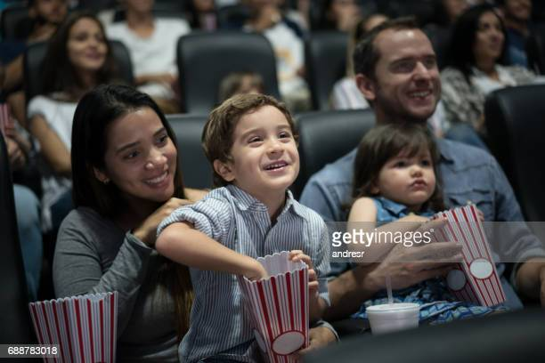 Portrait of a happy family at the movies eating popcorn