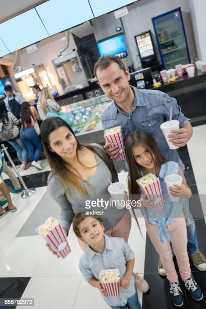 Portrait d'une famille heureuse d'avoir boissons et manger au cinéma