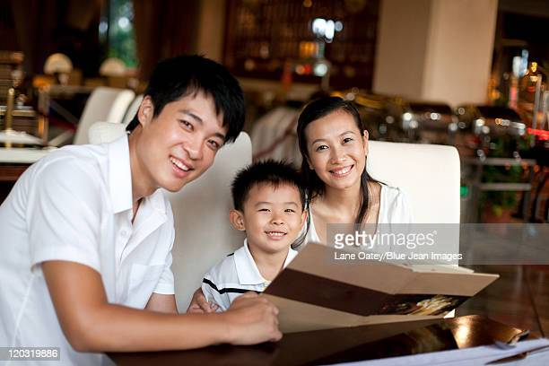 portrait of a happy family looking through a menu - short sleeved stock pictures, royalty-free photos & images