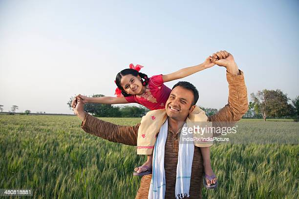 Portrait of a happy father carrying daughter on shoulders at farm against sky