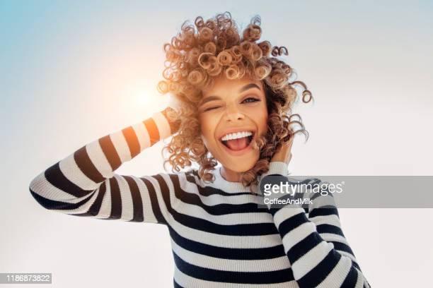 porträt eines glücklichen mädchens gegen blauen himmel - offenes lächeln stock-fotos und bilder
