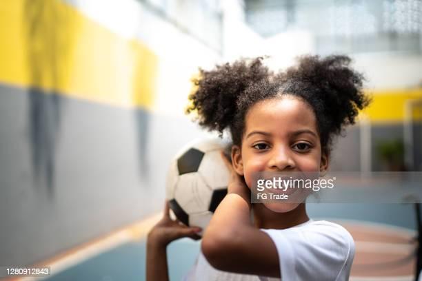 retrato de uma garota feliz segurando uma bola de futebol durante aula de atividade física - sporting term - fotografias e filmes do acervo
