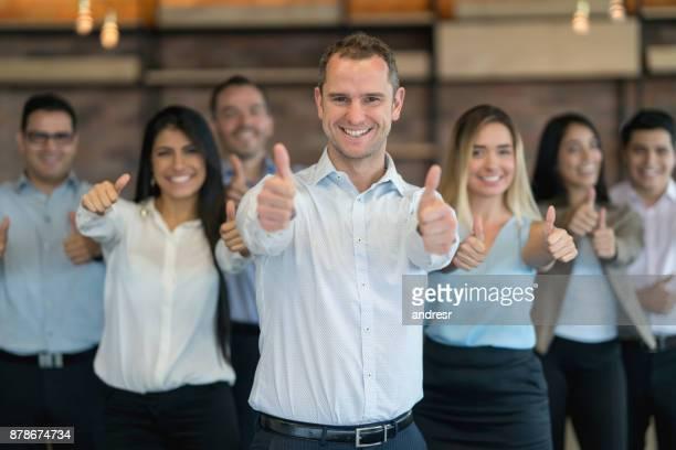 Portret van een gelukkig groep van mensen uit het bedrijfsleven op kantoor met Duimschroef opwaarts