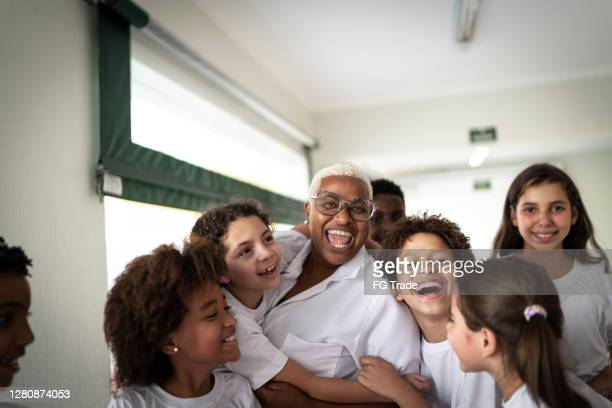 portrait of  a happy group of elementary students with teacher - state school stock pictures, royalty-free photos & images