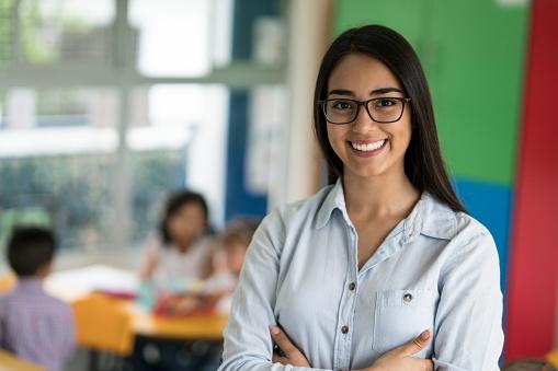Portrait of a happy Latin American teacher at the school 687830554