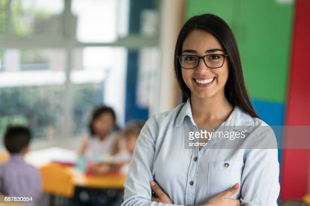 portrait of a happy latin american teacher at the school - teaching stock pictures, royalty-free photos & images