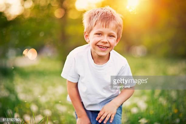 Ritratto di felice piccolo ragazzo in campo di dente di leone