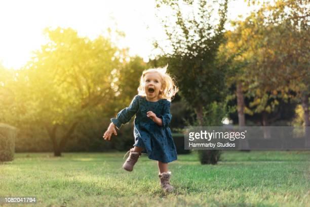 retrato de uma menina feliz correndo por sorrindo em um parque público - 2 3 anos - fotografias e filmes do acervo