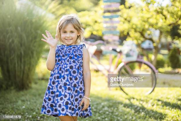 portrait of a happy little girl wearing dress, waving and looking at camera outdoors - waving gesture stock pictures, royalty-free photos & images