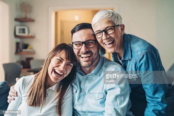 porträt einer glücklichen reifen frau mit ihrem erwachsenen sohn und ihrer schwiegertochter - kleine personengruppe stock-fotos und bilder