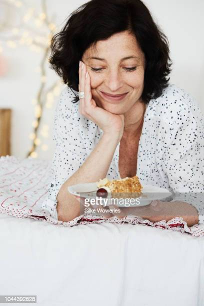 portrait of a happy mid adult woman holding a piece of cake