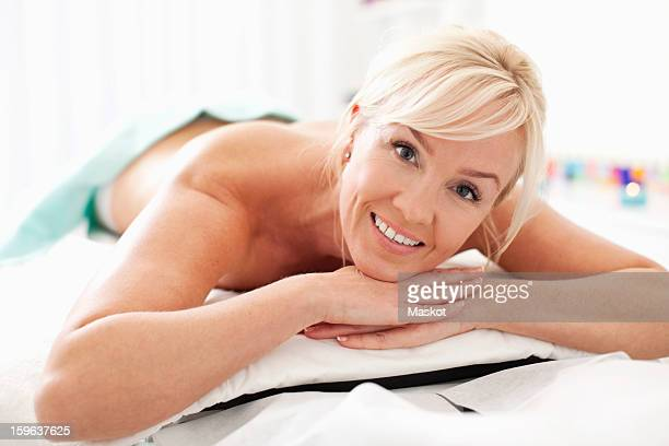 Portrait of a happy mid adult woman lying naked on massage table at health spa