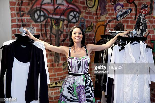 Portrait of a happy mid adult woman standing by clothes rack with graffiti in background