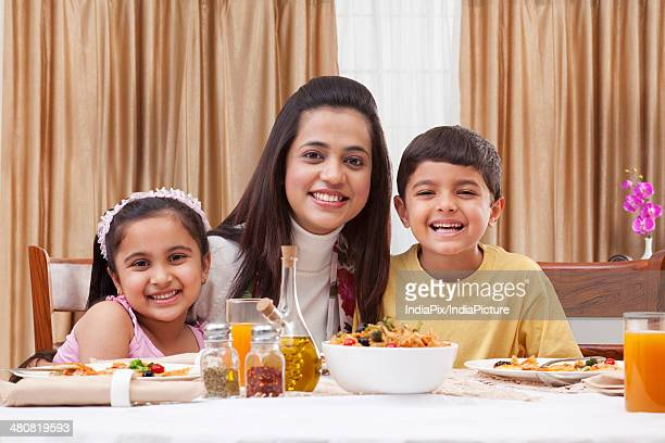 Portrait of a happy mother and children at restaurant table