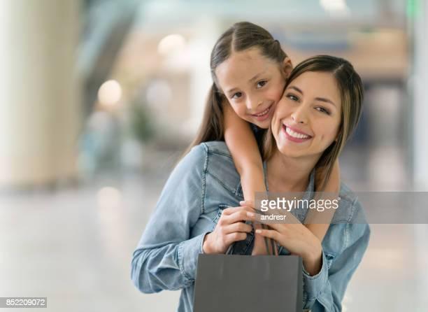 Porträtt av en glad mor och dotter på shopping center