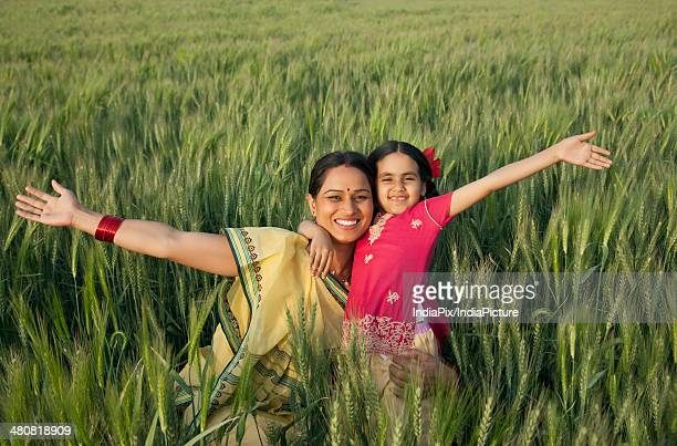 Portrait of a happy mother and daughter with arms outstretched in field