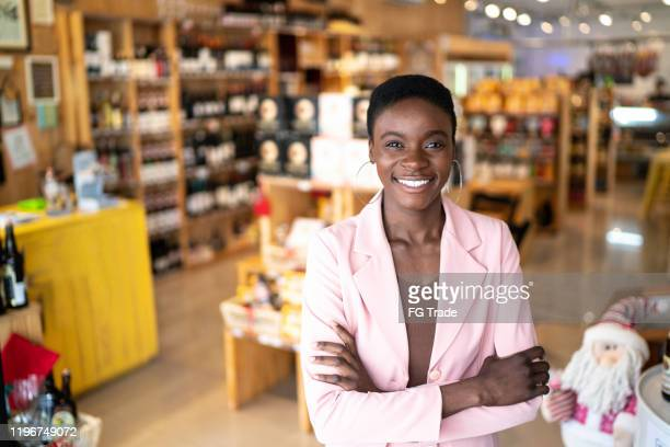 portrait of a happy owner / businesswoman standing with arms crossed in a store - pardo brazilian stock pictures, royalty-free photos & images