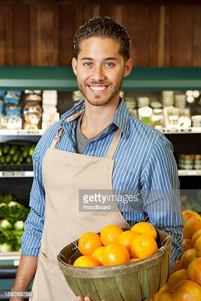 Portrait of a happy salesperson with basket full of oranges in market