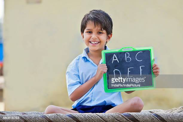 Portrait of a happy school boy holding slate with English alphabet on it