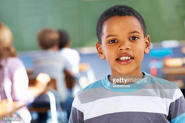 Portrait of a happy school boy in the classroom