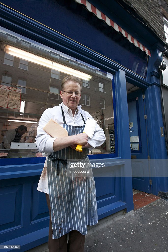 Portrait of a happy senior butcher standing outside shop with cleaver : Stock Photo