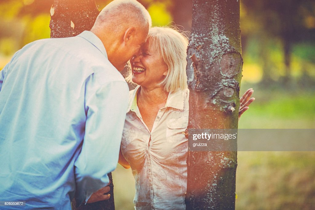 Portrait of a happy senior couple having fun, embracing and kissing in the public park at sunset : Stock Photo