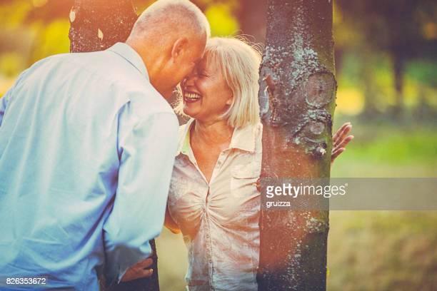 Portrait of a happy senior couple having fun, embracing and kissing in the public park at sunset