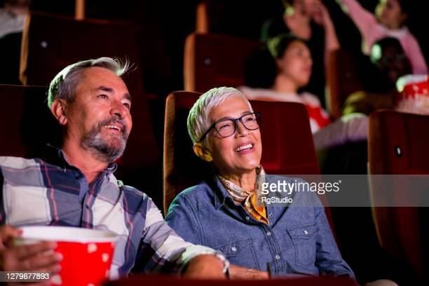portrait of a happy senior couple watching a relaxing movie at the cinema - film industry stock pictures, royalty-free photos & images