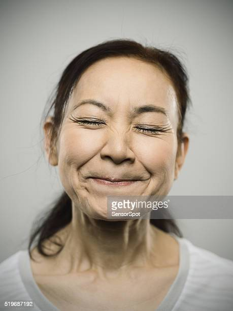 portrait of a happy senior japanese woman with closed eyes. - fine art portrait stock photos and pictures