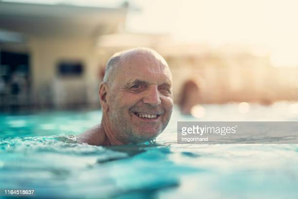 portrait of a happy senior man enjoying swimming pool - imgorthand stock photos and pictures
