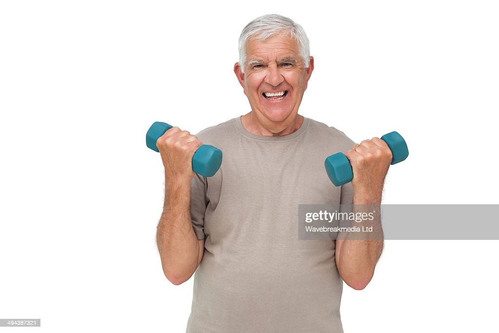 Portrait of a happy senior man exercising with dumbbells : Stock Photo