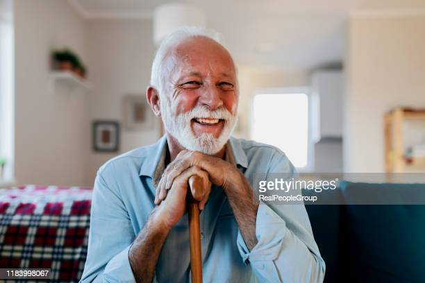 portrait of a happy senior man sitting and holding his walking stick in a nursing home during the morning - medicare stock pictures, royalty-free photos & images