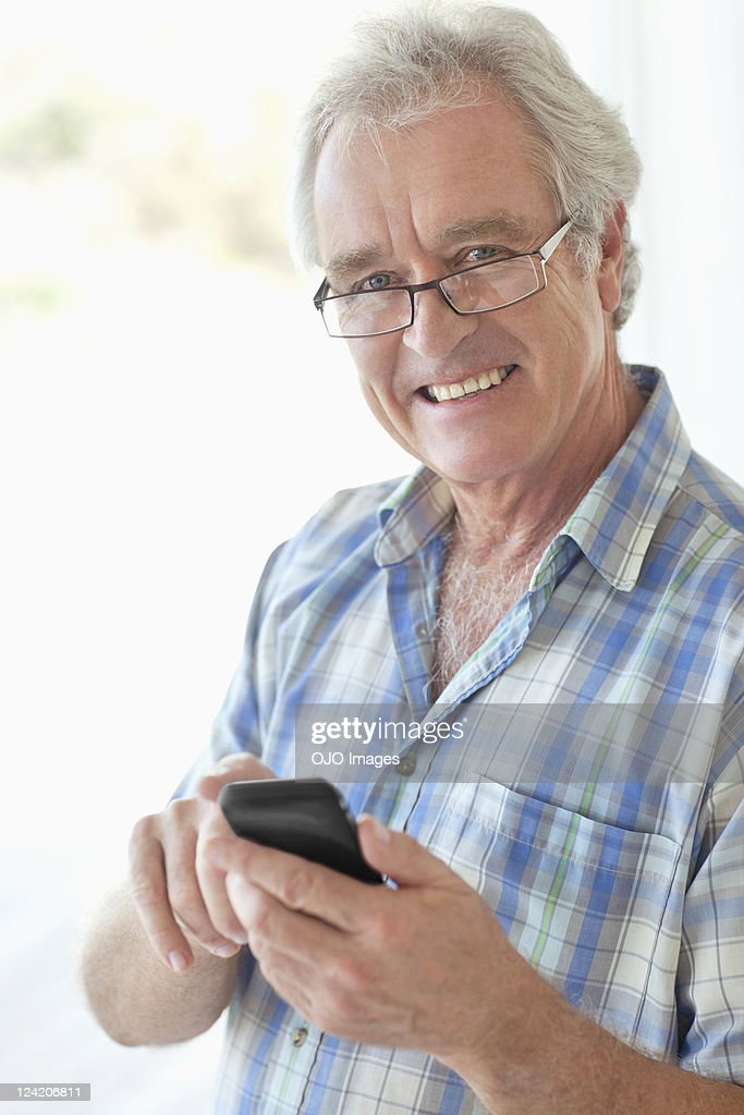 Portrait of a happy senior man text messaging on mobile phone : Stock Photo