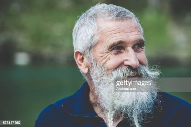 retrato de um homem feliz sênior com barba branca e bigode pelo rio soca, eslovénia - só um homem idoso - fotografias e filmes do acervo