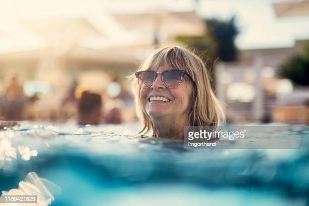 retrato de uma mulher sênior feliz que aprecia a piscina - vida real - fotografias e filmes do acervo