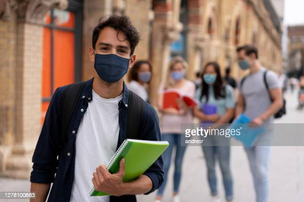 portrait of a happy student wearing a facemask on the street - studying stock pictures, royalty-free photos & images