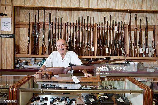 portrait of a happy weapon shop owner - gun shop stock photos and pictures