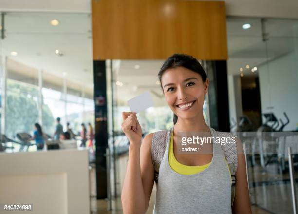 Portrait of a happy woman at the gym holding a loyalty card