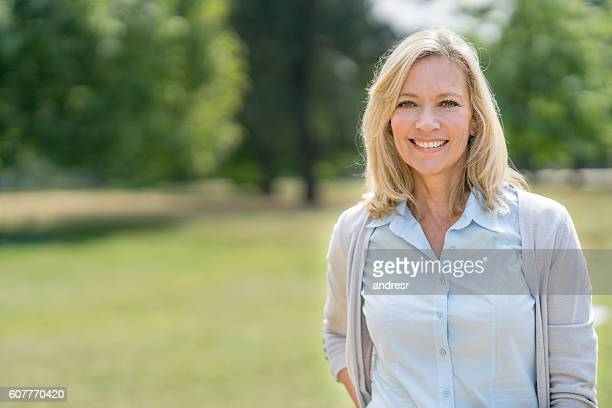 portrait of a happy woman at the park - natural blonde stock photos and pictures