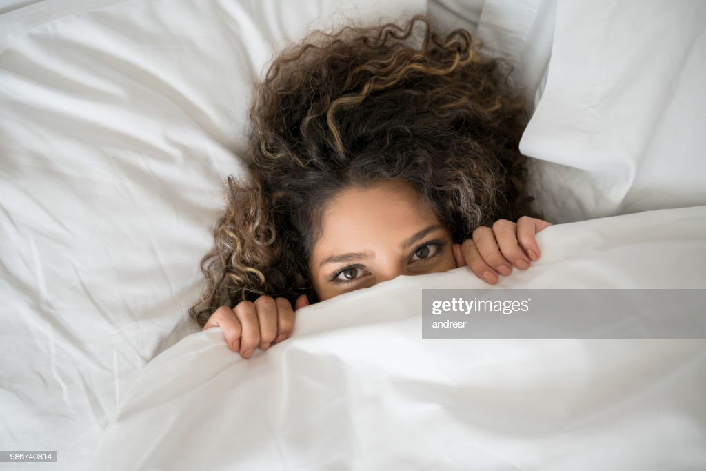 Portrait of a happy woman in bed : Stock Photo