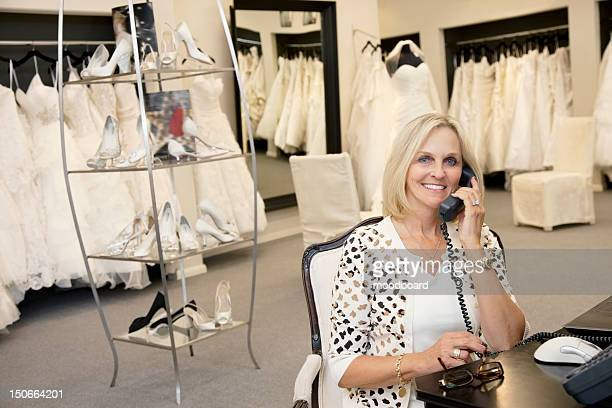 portrait of a happy woman making a call in bridal store - alleen één seniore vrouw stockfoto's en -beelden