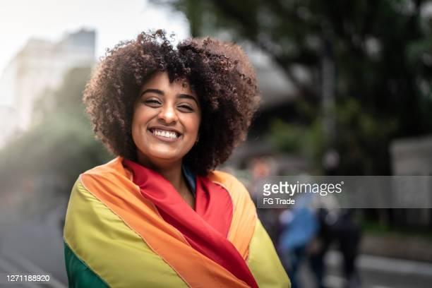 verticale d'une femme heureuse utilisant le drapeau d'arc-en-ciel - lesbienne photos et images de collection