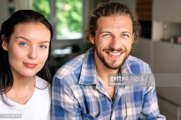 portrait of a happy young couple at home - heteroseksueel koppel stockfoto's en -beelden