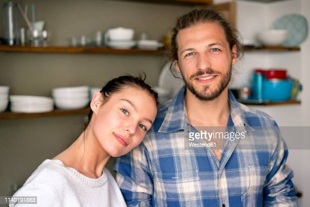 portrait of a happy young couple at home - young couple stock pictures, royalty-free photos & images